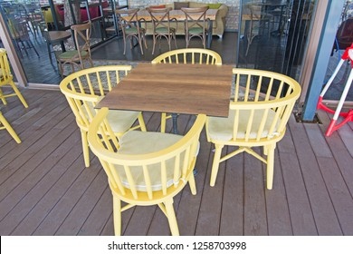 Set of wooden chair and table with four side sitting arrangement hotel outdoor