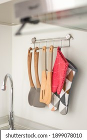 Set of wooden kitchen utensils and oven mitt hanging on white wall over washing tap in small kitchen.