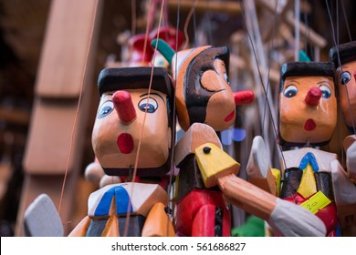 Set of wooden pinocchio dolls with his long nose on a white background