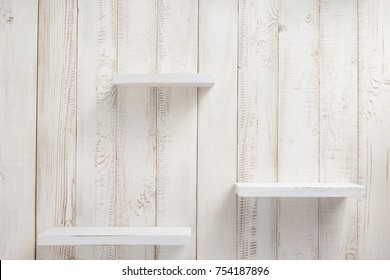 set of wooden shelves on white wall background texture