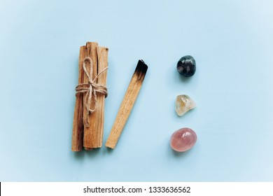 A set of wooden sticks Palo Santo on a blue background. Nearby are special stones - minerals. They are used in religious ceremonies.