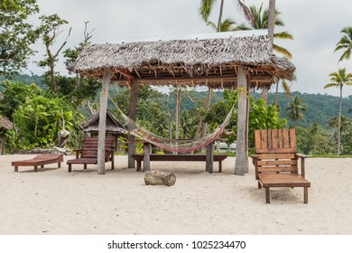 Set of wooden stools and tables for visitors placed under coconut palm trees on the white sands of the beach facing Malet island.
