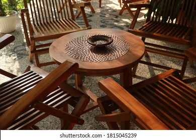 Set of wooden table and chairs in the garden. Teak wood furniture stand on the terrace