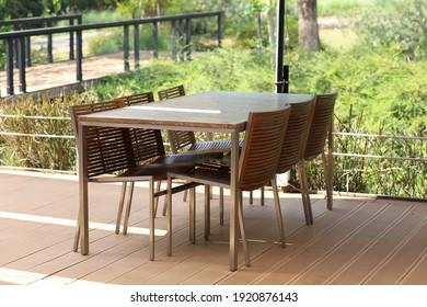 Una mesa y sillas de madera en una terraza cerca del jardín