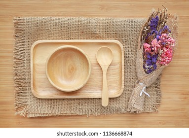 Set of wooden tray, bowl and spoon on sack against wood board background
