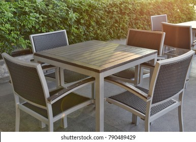 A set of wooden-steel table and rattan chairs is provided on sharing area with warm sunlight on a roof deck floor beside a pool for residence' s dweller to take rest in their hobbies time for relaxing