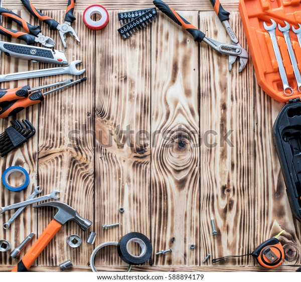 A set of working tools on a wooden background