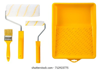 Set of yellow paint tray with paint rollers and brush on light background