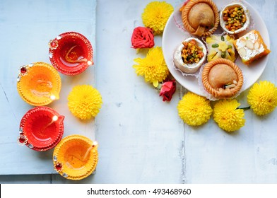 Set of yellow and red diyas on a blue background with flowers and sweets or mithai