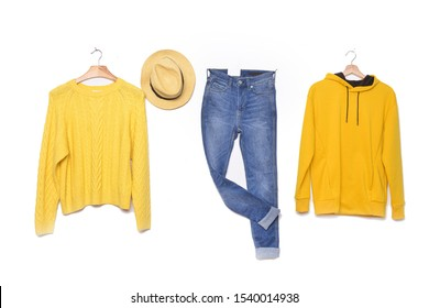 Set of yellow sweater , hoodie, sweatshirt on hanging with blue jeans are hanging and hat