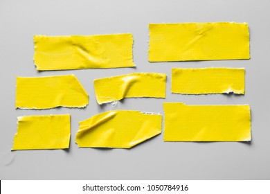 Set of yellow tapes on gray background. Torn horizontal and different size black sticky tape, adhesive pieces.