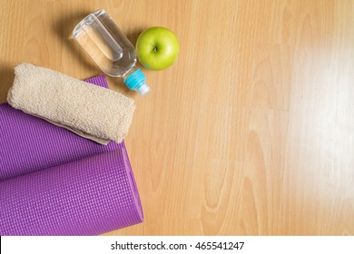Set for yoga practice with purple mat, towel, bottle of water and green apple,  Exercise equipment. Top view and Copy space.