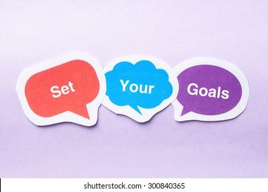 Set your goals concept paper bubbles against purple background.