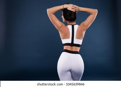Set your goals high, and do not stop till you get there. Beautiful sexy fitness girl showing her strong muscles and sexy butt on dark background while holding her hair.