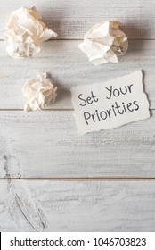 Set your priorities reminder handwriting on a paper note with crumpled paper ball.