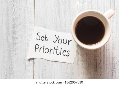Set your priorities reminder handwriting on a paper note with a cup of espresso coffee.
