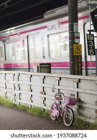Setagaya, Tokyo, JAPAN - August 11, 2020: A kid's pink bicycle along the tracks while a train from Keio Line is passing in Japan near the Kamikitazawa Station.