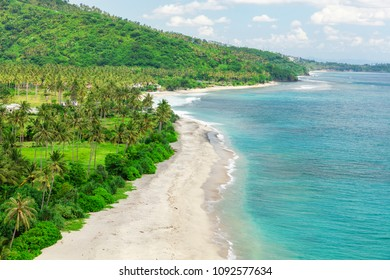 Setangi beach with white sand, blue water and palm trees, Lombok, Indonesia
