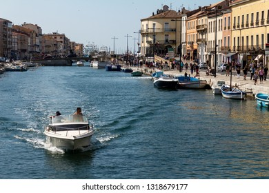 Sete, France - May 20, 2018. People walking on the sidewalks next to the canal of the city of Sete in France on May 20, 2018 at noon.  small boat circulates through the water.