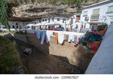 Setenil, Spain - March 4th, 2019: Street with dwellings built into rock overhangs. Setenil de las Bodegas, Cadiz, Spain. Sunny caves neighborhood