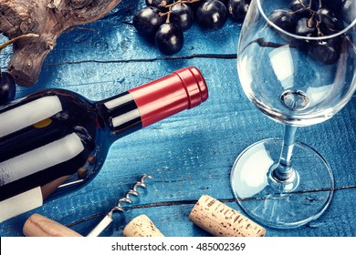 Setting with bottle of red wine, grape and corks. Wine list concept over blue background