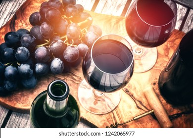 Setting with bottles of red wine, wine glasses and grape