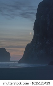 Setting crescent moon next to large cliff face on coast of Olympic National Park in Washington.