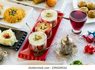 Setting Feast Table with magnolia pudings,rice,Ramadan dessert gullac and sherbet on the handmade lace tablecloth.Sugar Feast end of Ramadan or any Feast celebration concept.