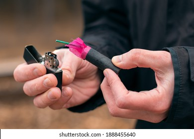 Setting Fire to the Firecracker. Man in Black Clothes Lighting Up the Petard. Firing Up the Pyrotechnics with a Black Gasoline Lighter Outdoors