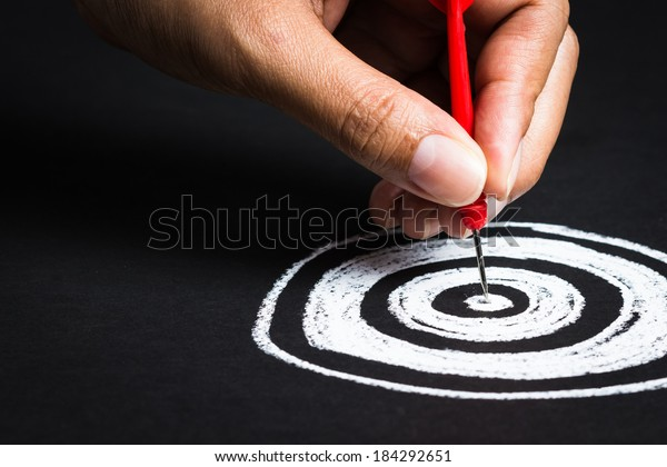 Setting goal or accurate planning, hand going to take dart into the center of sketching dartboard