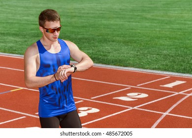 Setting goals. Horizontal shot of a fit and toned young male athlete looking at his watch after running sprint on the stadium
