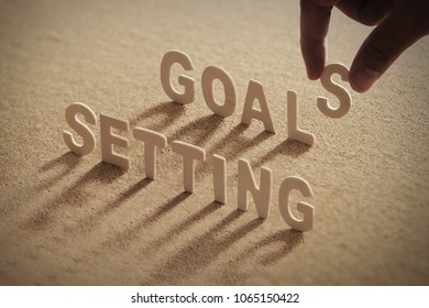 SETTING GOALS wood word on compressed or corkboard with human's finger at S letter.