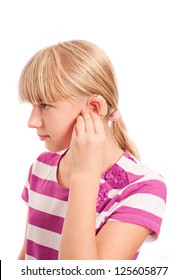 Setting a Hearing aid - Young female setting her hearing aid isolated on white