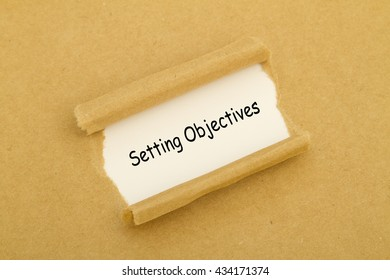 Setting Objectives written under torn paper.