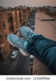 Setting on a tall building. Sneaker in rooftop. Sneaker in the edge of a building.