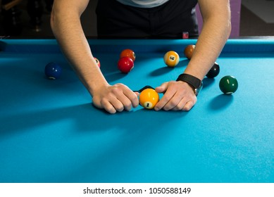 Setting a rack of 9 ball in pool, billiard on a special rack, blue cloth billiard table. Assembling the rack, starting with 1 ball.