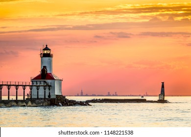 The setting sun back lights the lighthouse shining at Michigan City, Indiana with a rare superior mirage vision of the Chicago skyline on the horizon across the southern end of Lake Michigan.