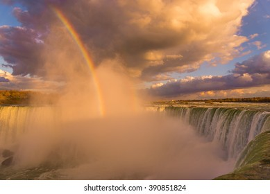 The setting sun casts a golden and pink glow on the mist rising from Niagara Falls.