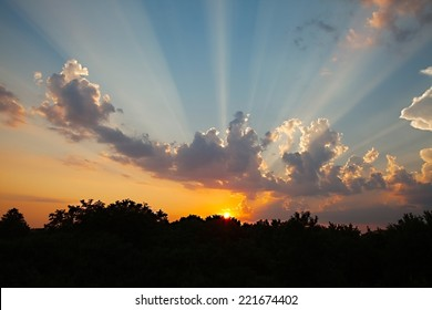 Setting sun in cloudy sky