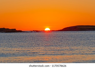 The setting sun dips below the horizon, between two small islands out in the Celtic Sea near Landeda, Brittany.