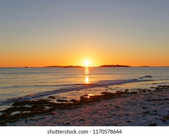 The setting sun dips between two small islands in the Celtic Sea.