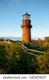 Setting sun illuminates the brick tower of Aquinnah lighthouse on the island of Martha's Vineyard in Massachusetts. It is one of New England's largest islands.
