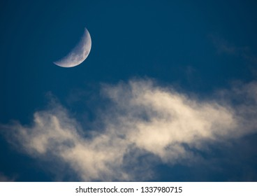A setting sun illuminates a crescent moon and wispy clouds on a dark blue background.