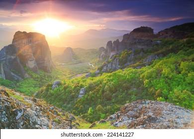 Setting sun illuminates green valley and the monasteries of Meteora, Greece