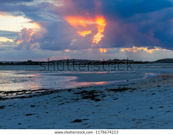 The setting sun on Plage Sainte-Marguerite,  peeks through the holes in the clouds
