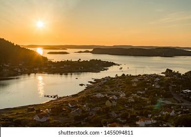 Setting sun over Archipelago of Rörtången and big island Brattön Sweden - Low sun casts light over reflecting sea and valley.