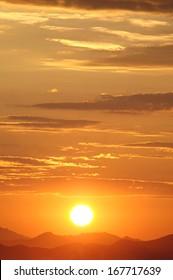 Setting sun over hills in the desert