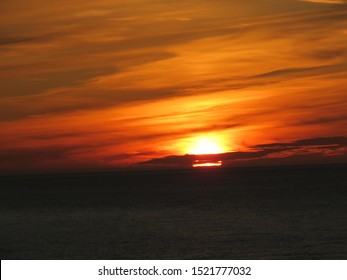 The setting sun paints the sky a psychedelic colour in all hues of orange and red with the horizon a dark black colour