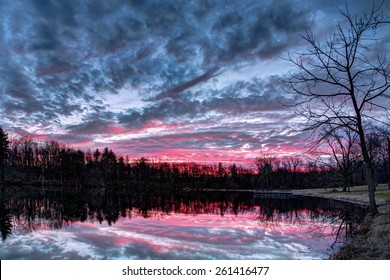 The setting sun paints the sky with vivid and dramatic colors that is reflected on a small Indiana pond in Sodalis Nature Park.