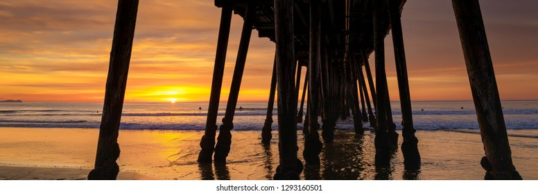 The setting sun at the pier in Imperial Beach, California with the silhouettes of surfers waiting for waves.